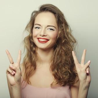 Bella giovane donna sorridente che mostra i pollici aumenta il gesto