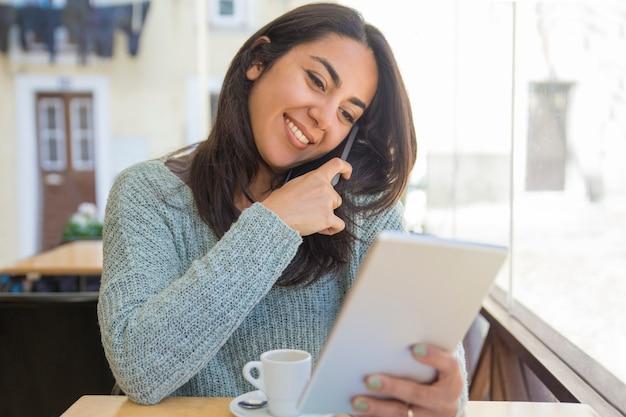 Bella giovane donna sorridente che per mezzo dello smartphone e della compressa