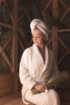 Bella giovane donna sorridente che si siede sul banco alla sauna