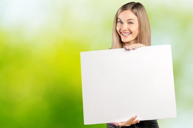 Bella giovane donna sorridente felice in abbigliamento casual astuto rosa che mostra insegna in bianco