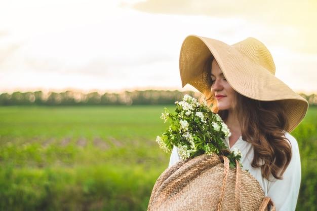 Bella giovane donna sorridente in abito vintage e cappello di paglia in fiori di campo di campo. la ragazza tiene in mano un cesto di fiori