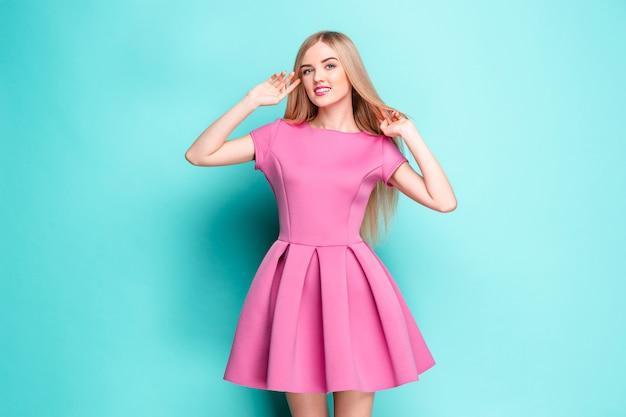 Bella giovane donna sorridente in mini vestito rosa che posa allo studio