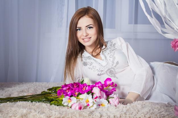 Bella giovane donna sorridente in vestito bianco che pone su un letto con i fiori
