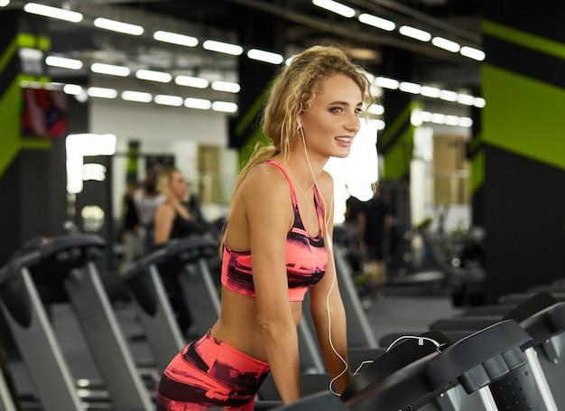 Bella giovane donna sportiva che funziona sulla pedana mobile in ginnastica e che ascolta la musica