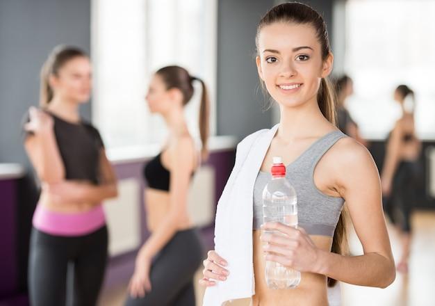 Bella giovane donna sportiva con acqua in palestra.