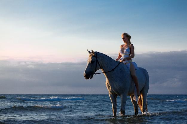Bella giovane donna su un cavallo vicino al mare