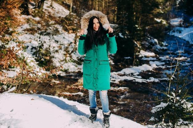 Bella giovane donna su un'escursione in una foresta di inverno