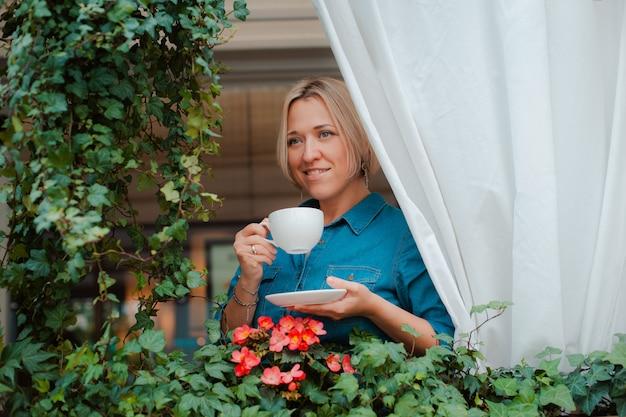 Bella giovane donna sul balcone con fiori e tenda bianca godendo una tazza di caffè al mattino.
