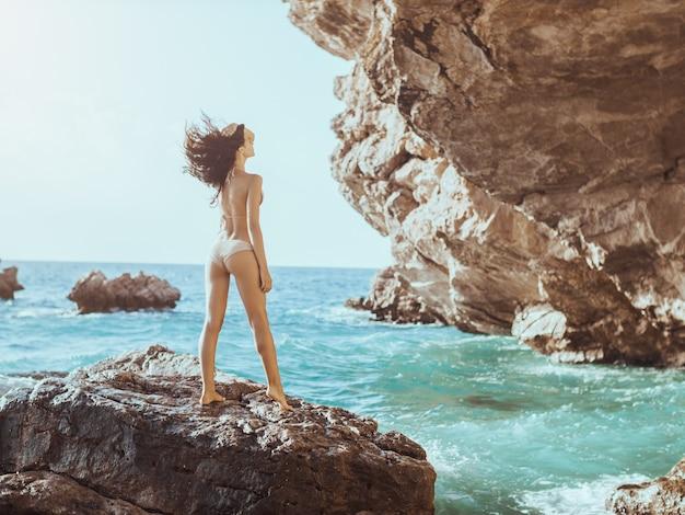 Bella giovane donna sulla spiaggia rocciosa selvaggia.