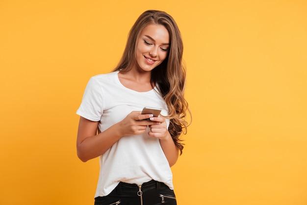 Bella giovane donna sveglia allegra che chiacchiera dal telefono cellulare