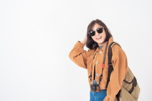 Bella giovane donna turistica asiatica felice sulla parete bianca