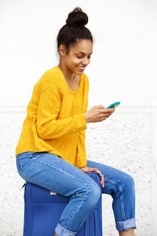Bella giovane donna utilizzando il telefono cellulare e seduto sulla valigia