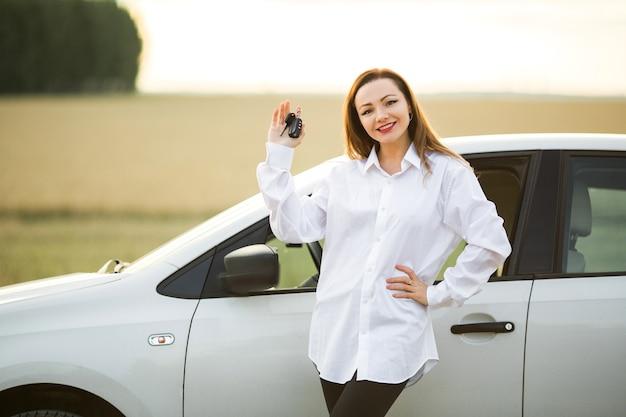 Bella giovane donna vicino alla macchina
