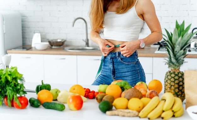 Bella giovane donna vicino nella cucina con alimento sano.