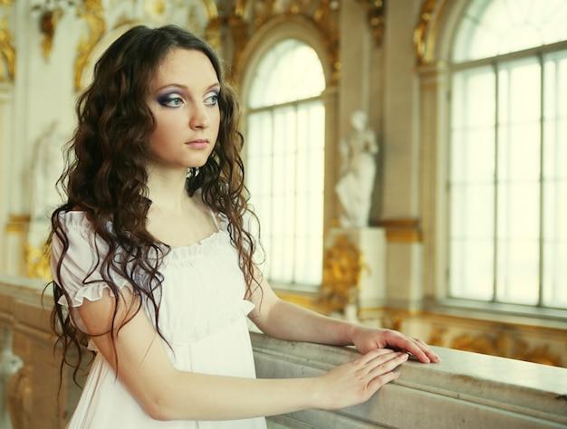 Bella giovane donna vittoriana in abito bianco