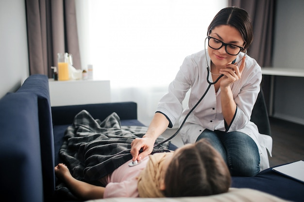 Bella giovane dottoressa ascolta il respiro del bambino attraverso lo stetoscopio. lei sorride e guarda la ragazza. il dottore si siede inoltre. bambino sdraiato sul divano.