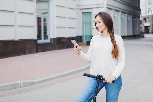 Bella, giovane e una ragazza dai denti bianchi con lunghi capelli castani si fermò mentre cavalcava lo scooter