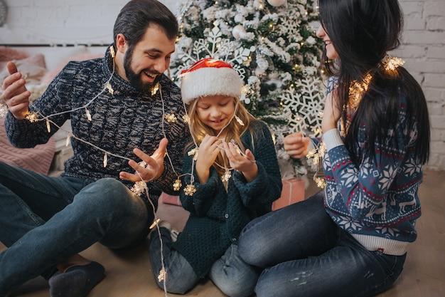 Bella giovane famiglia che si gode le vacanze insieme, decorando l'albero di natale, organizzando le luci di natale e divertendosi