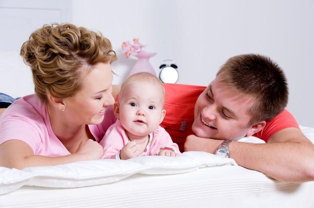 Bella giovane famiglia felice con il bambino sorridente sdraiato sul letto di casa