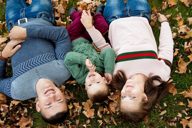 Bella giovane famiglia in una passeggiata nella foresta di autunno.