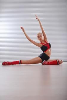 Bella giovane femmina atletica che allunga prima del suo allenamento