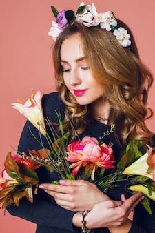 Bella giovane femmina con lunghi capelli biondi ondulati in corona di fiori primaverili in posa con bouquet di fiori su sfondo rosa.