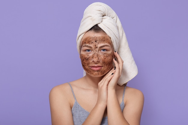 Bella giovane femmina con maschera al cioccolato sul viso, pone con un asciugamano bianco sulla testa