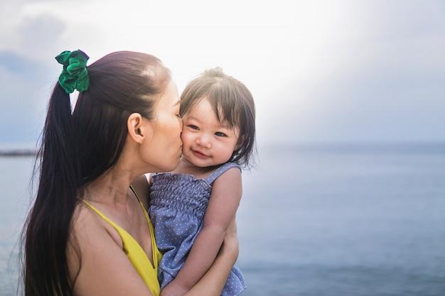 Bella giovane madre con la figlia sullo sfondo spiaggia