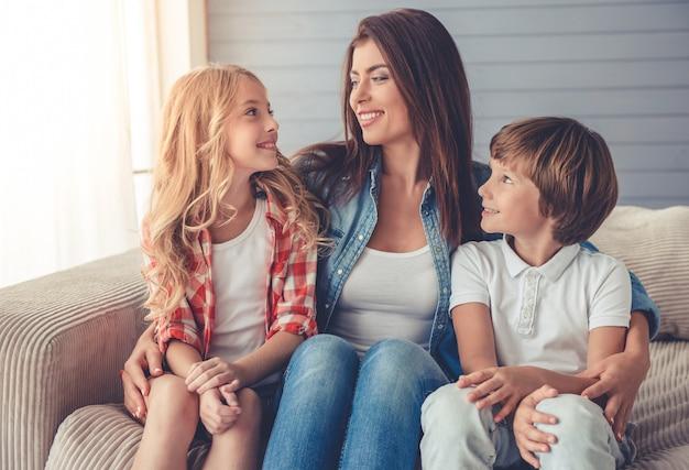 Bella giovane madre e i suoi figli stanno parlando