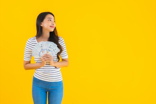 Bella giovane manifestazione asiatica della donna del ritratto molti contanti o soldi del dollaro