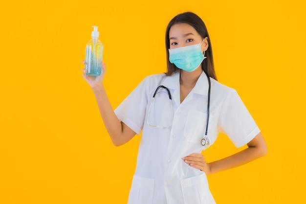 Bella giovane maschera asiatica di usura della donna di medico del ritratto con il gel dell'alcool