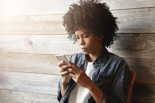 Bella giovane ragazza africana hipster con capelli ricci che indossa abiti alla moda tenendo il telefono cellulare