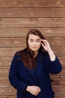 Bella giovane ragazza alla moda nel fondo di legno
