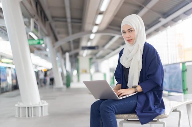 Bella giovane ragazza asiatica che lavora ad uno skytrain con un computer portatile. donne musulmane