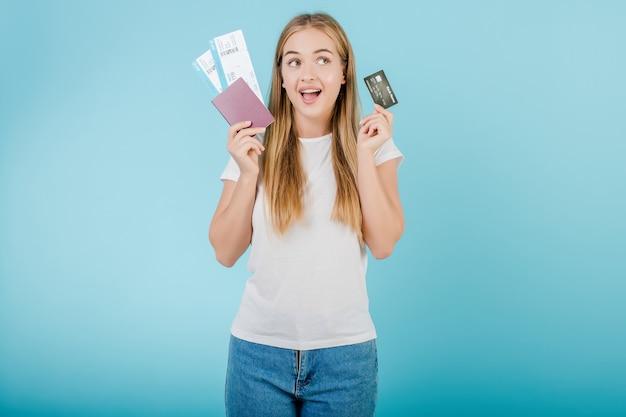 Bella giovane ragazza bionda con il passaporto e la carta di credito isolata sopra il blu