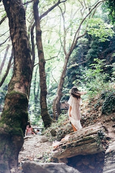 Bella, giovane ragazza cammina ai piedi della montagna lungo