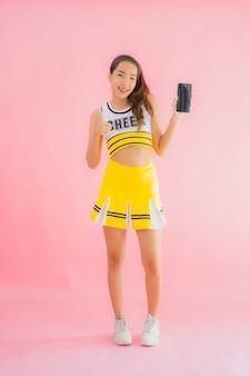 Bella giovane ragazza pon pon asiatica della donna del ritratto con il telefono cellulare astuto