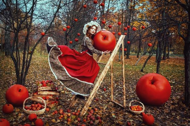 Bella giovane ragazza sexy con le mele rosse nel giardino di autunno