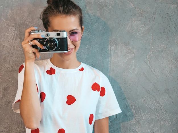 Bella giovane ragazza sorridente del fotografo che prende le foto usando la sua retro macchina fotografica.