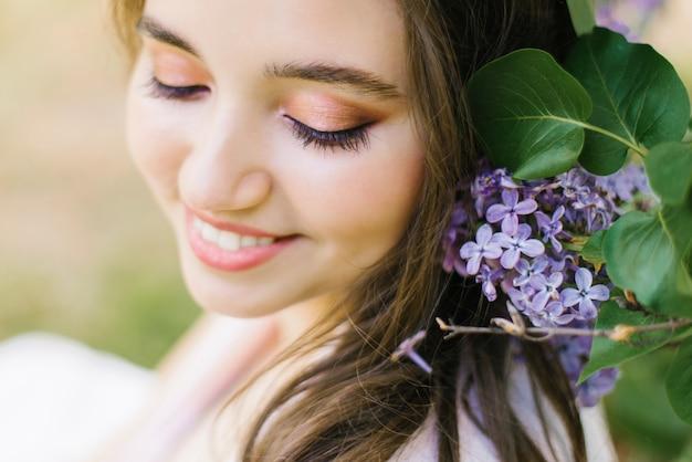 Bella giovane ragazza sveglia con la fine professionale di trucco alta e l'abbagliante sorriso bianco con i fiori lilla felici