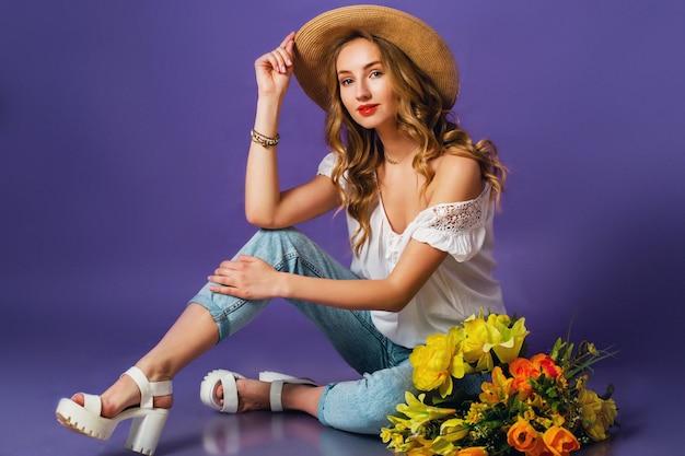 Bella giovane signora bionda in cappello alla moda di estate della paglia che tiene il mazzo variopinto del fiore della molla vicino al fondo porpora della parete.