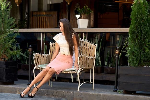 Bella giovane signora che si siede sul banco di metallo vicino al terrazzo del caffè