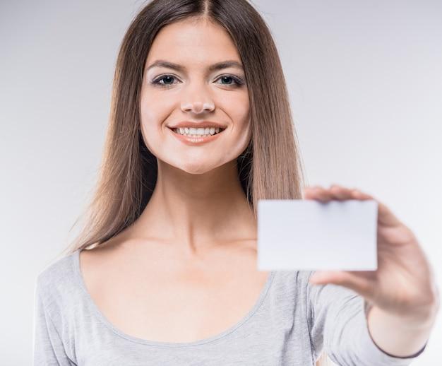 Bella giovane signora che sorride e che mostra biglietto da visita in bianco.