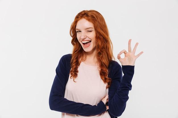 Bella giovane signora felice di redhead che mostra gesto giusto.