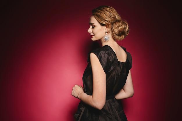 Bella giovane signora in vestito nero elegante con trucco e gli orecchini di sera che posano con gli occhi chiusi a fondo rosa, foto alla moda di fascino