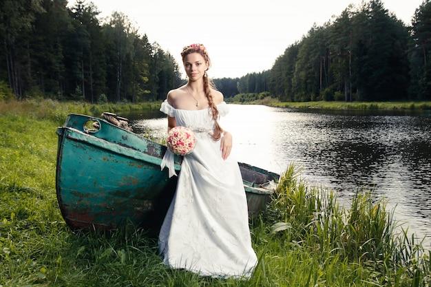 Bella giovane sposa che si siede sulla barca