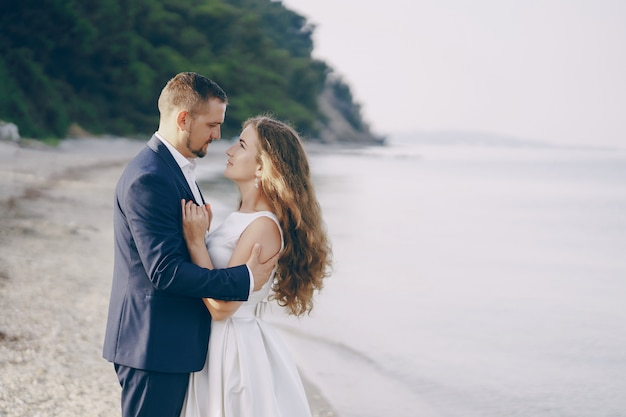 Bella giovane sposa dai capelli lunghi in abito bianco con il suo giovane marito sulla spiaggia