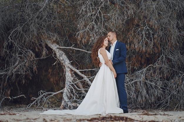 Bella giovane sposa dai capelli lunghi in abito bianco con il suo giovane marito vicino filiali