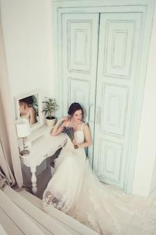 Bella giovane sposa in abito da sposa bianco