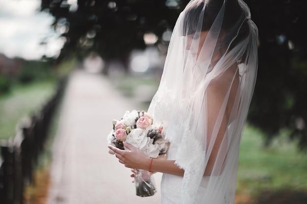 Bella giovane sposa in un vestito di lusso bianco e in un velo da sposa con un mazzo di fiori in posa all'aperto. ritratto di nozze. copia spazio